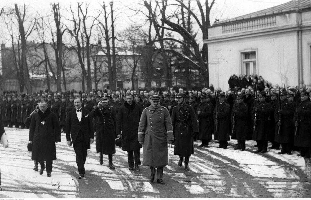 Józef Piłsudski (pierwszy plan, nieco z przodu) idzie przed frontem oddziału Kolejowego Przysposobienia Wojskowego Okręgu Warszawskiego. Widoczny między innymi minister Alfons Kuhn (pierwszy plan, czwarty z lewej)