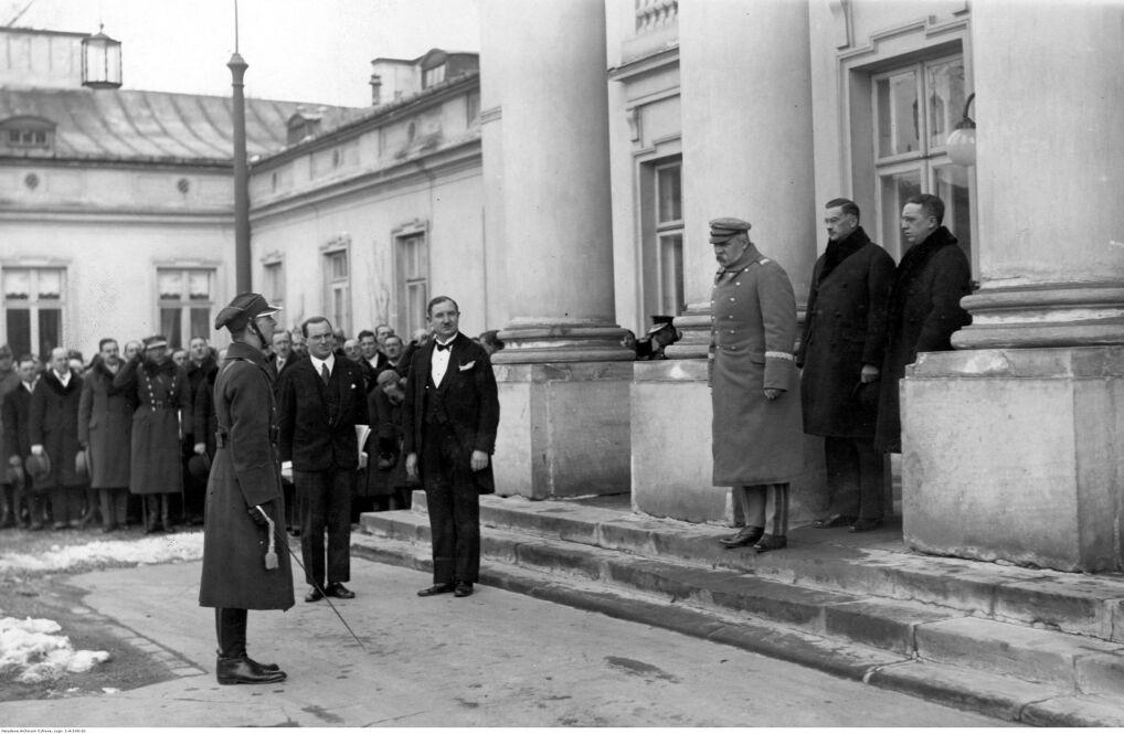 Józef Piłsudski (trzeci z prawej) przyjmuje życzenia imieninowe od delegacji Kolejowego Przysposobienia Wojskowego Okręgu Warszawskiego. Widoczni między innymi: minister Alfons Kuhn (drugi z prawej), Gustaw Rożałowski (pierwszy z prawej) oraz składający raport kpt. Starzak (pierwszy plan, pierwszy z lewej)