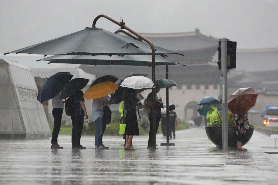 Mieszkańcy próbują schronić się przed intensywnym deszczem w centrum Seulu w Korei Południowej