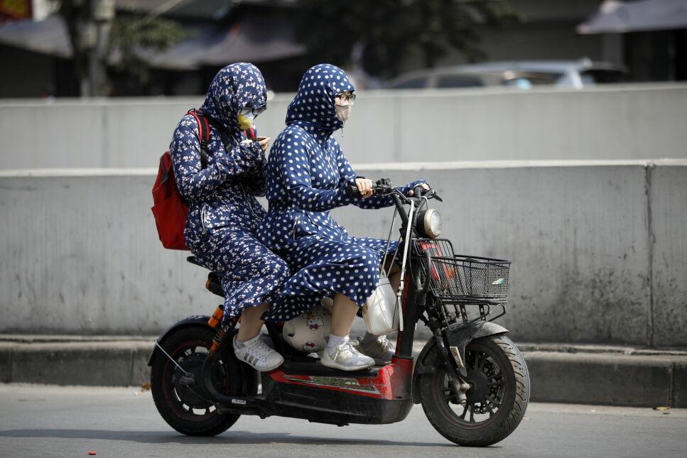 W północnym i środkowym Wietnamie panują ekstremalne upały, ludzie chronią się przed nimi zakrywając ciało ubraniami, Hanoi, Wietnam