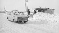 Grupa osób oczekujących na przystanku PKS w Starych Babicach pod Warszawą, luty 1979 r. Na drodze taksówka skoda 100